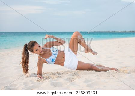 How to do a Side Plank Crunch fitness instruction demonstration physical trainer on beach training obliques stomach muscles doing core body training. Fit girl exercising doing abs exercise.