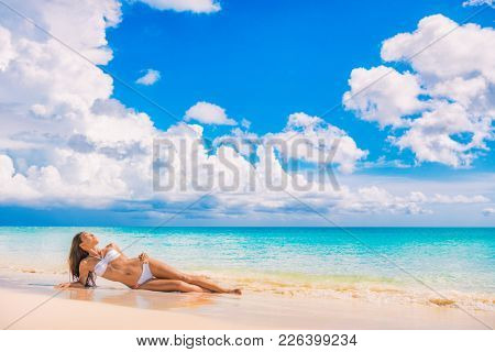 Beach travel vacation paradise sexy bikini woman lying down on sand relaxing sun tanning in tropical caribbean travel destination for summer vacation. Asian swimsuit model girl.