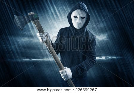 Masked armed poacher in mysterious rainy coastal weather concept