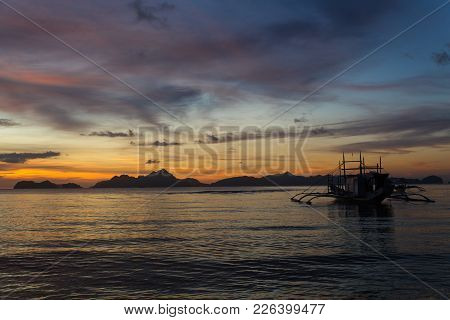 Traditional Philipinian Boat Silhouette In El Nido, Palawan With Colored Sunset On Background