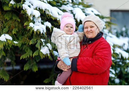 Beautiful Grandmother Holding Baby Girl In Pram During Snowfall In Winter. Happy Family. Carefree Ch