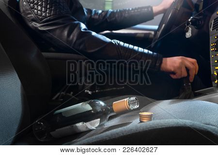 Drunk Driving Concept. Young Man Driving Car Under The Influence Of Alcohol. Empty Bottle Of Wine On