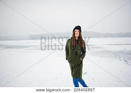 Funny Girl Wear On Long Green Sweatshirt, Jeans And Black Headwear, At Frozen Lake In Winter Day.