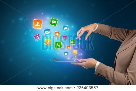Hand holding tablet and application icons falling inwards