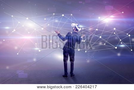 Young businessman standing with vj glasses and checking life-sized connectivity project