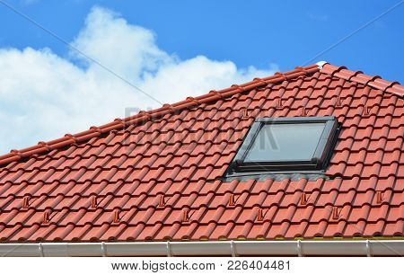 Attic Window Skylights On The Red Clay Tiled Roof.