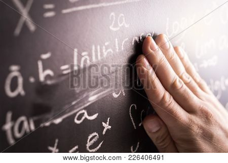 Making Mistakes And Wrong Answer Concept. Hand Wiping Math Formula Off Blackboard In Classroom At Sc