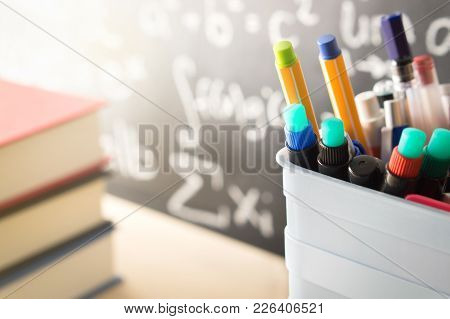 Pen Holder And Books In Front Of Blackboard In Classroom. Education, Learning, Teaching And Knowledg
