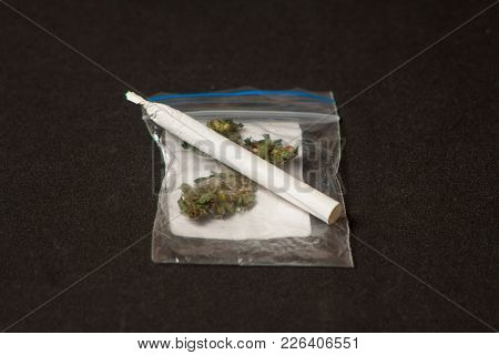 Leaves And Seeds Of Marijuana With Two Cigarettes For Smoking