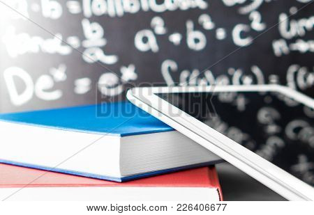 E Learning And Modern Education Concept. Smart Mobile Device And Tablet With Stack Of Colorful Books