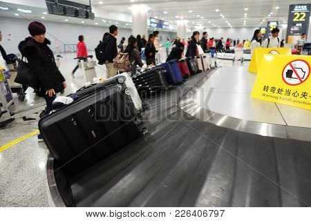 Shanghai, China-jan 08, 2018: Travelers Waiting For Luggage From Conveyor Belt At Shanghai Airport,