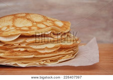 Stack Of Tinny Pancakes On Kitchen Table With Copy Space.