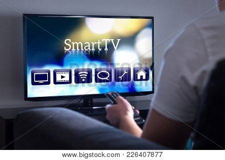 Man Watching Smart Tv. Choosing Movie Or Series From The Menu. Person Holding Remote Control. User I
