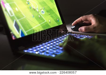 Young Man Playing Soccer Or Football Game Online With Laptop In Dark Or Late At Night. Competitive V