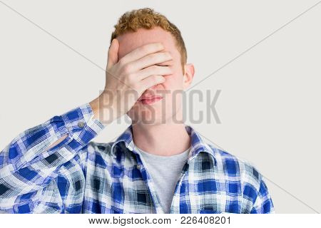 Annoyed Red Haired Caucasian Guy Covering Eyes With Hand. Young Man Suffering From Headache. Upset S