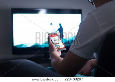 Man Reading Online News On Smartphone At Home. Mobile Phone News Website, Application Or Portal On C