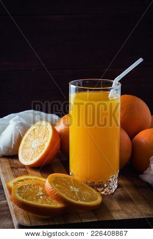 A Glass Of Orange Juice, Cut Into Pieces Orange, Oranges On A Wooden Board, White Cloth, Dark Backgr