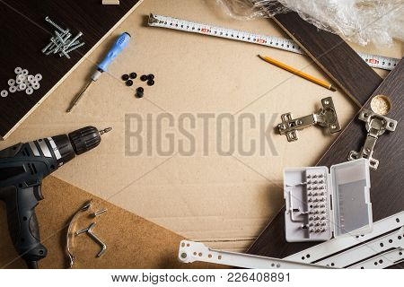 Tools, Furniture Parts, Wrapping Film, Screws On A Sheet Of Cardboard. Building Furniture Manually.
