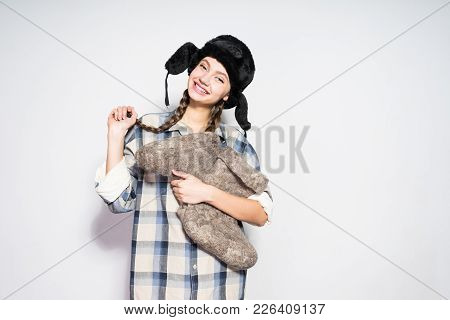 Cute Young Russian Girl In A Hat With Ear-flaps Holds Warm Felt Boots In Hands