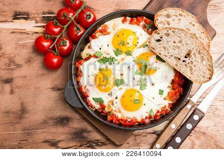 Tasty And Healthy Shakshuka In A Frying Pan. Fried Eggs With Tomatoes, Bell Pepper, Vegetables And H