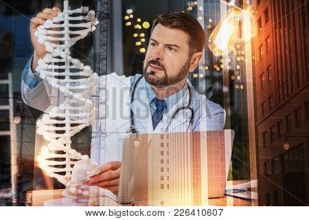 Genetic Analysis. Calm Concentrated Professional Geneticist Thoughtfully Looking At The Big Dna Mode
