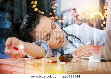 Feeling Bad. Tired Young Doctor Feeling Unwell And Having A Nap At Her Workplace With Colorful Pills