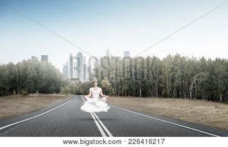 Young Woman Keeping Eyes Closed And Looking Concentrated While Meditating On Cloud Above The Road Wi