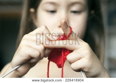 The Little Girl Concentrated On Knits On The Needles Of Red Wool Yarn