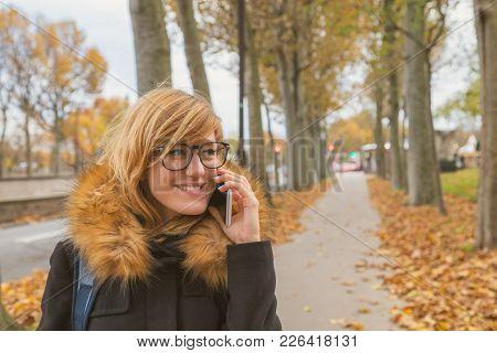 Cute Woman Walking On A Sidewalk In Autumn Surroundings.