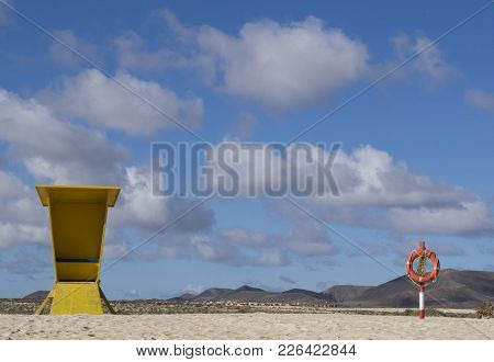 Yellow Lifeguard Stand And Red Lifebuoy On Sand  With Volcans And Bright Sky On Background