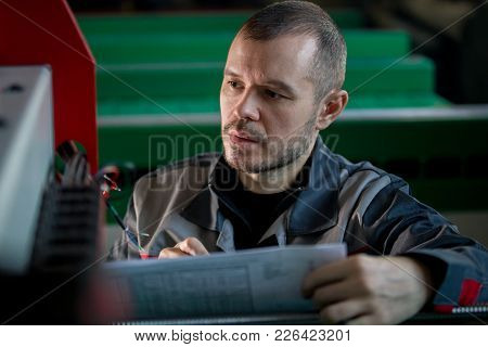 Man Worker Repairman Engineer During Work - Reads Paper Plan, Close Up