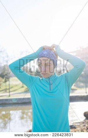 Sport Woman Tying Ponytail In The Park