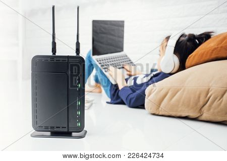 Wireless Router And Kids Using A Laptop In Home. Router Wireless Broadband Home Laptop Computer Phon