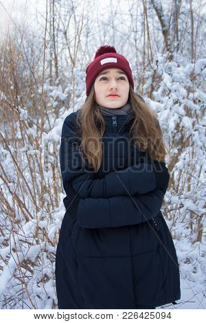 Beautiful Girl Freezing In Winter Forest. Portrait Of Serious Cute Attractive Young Teen Girl With L