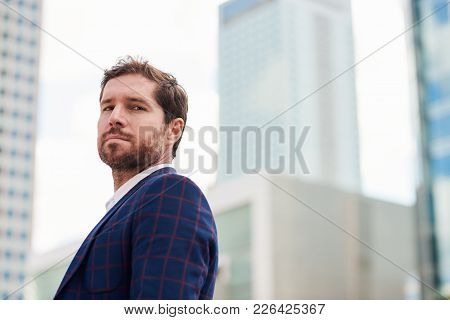 Confident And Successful Young Businessman Wearing A Blazer Standing Alone In The City With Office B