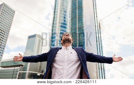 Ambitious Young Businessman Standing On A City Street In Front Of Office Buildings With His Arms Rai