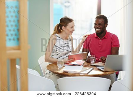 Two young intercultural managers laughing while discussing or watching funny things in the net at break by workplace