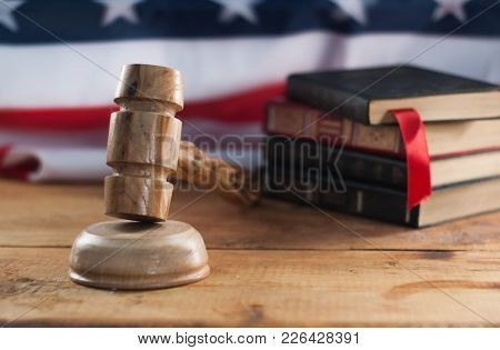 Judges Wooden Gavel With Usa Flag In The Background. A Symbol Of Jurisdiction. American Court