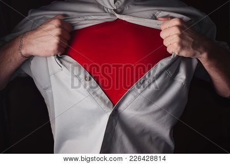 Superhero Tears Off His Shirt On A Dark Background. Tearing The Shirt On His Chest. Red T Shirt Hero