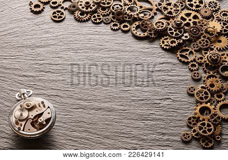 Various metal cogwheels and gear wheels with clockwork over slate background