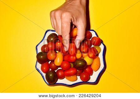 high angle view of the hand of a young caucasian man picking a tomato from a plate, in which there is an assortment of different cherry tomatoes, placed on a bright yellow background