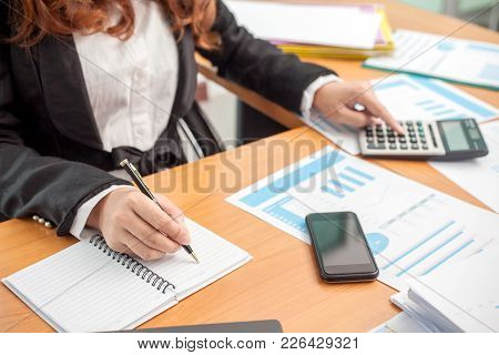 Business Woman At Working With Financial Reports And Laptop Computer In The Office