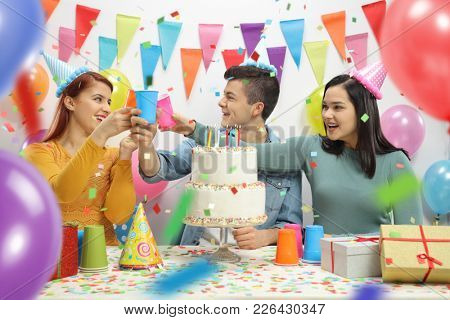 Cheerful teenagers celebrating a birthday and making a toast