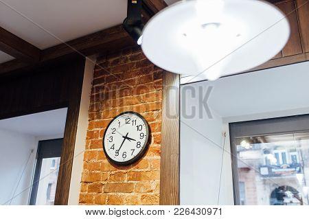 Classic Wall Clock On A Brick Wall. Loft Design In A Barber Shop
