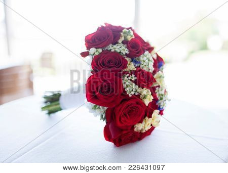 High key bridal bouquet of red roses.