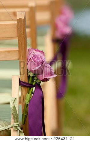 Pink roses tied to a chair for outdoor wedding ceremony,