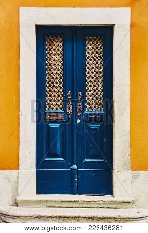 The Dark Blue Old Antique Door And The Yellow Corn-colored Wall. Soft Shadow And Photo Processing. C