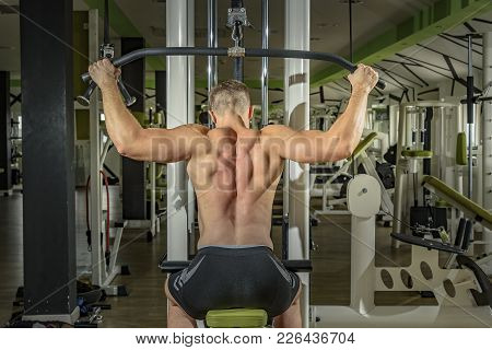 Shoulder Pull Down Machine. Fitness Man Working Out Lat Pulldown Training At Gym. Upper Body Strengt