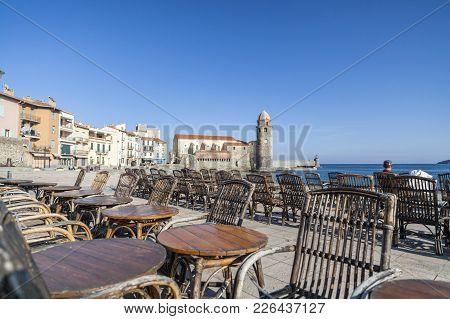 Collioure,france-november 30,2011: Mediterranean Beach,tower Church Ancient Building And Terrace Bar