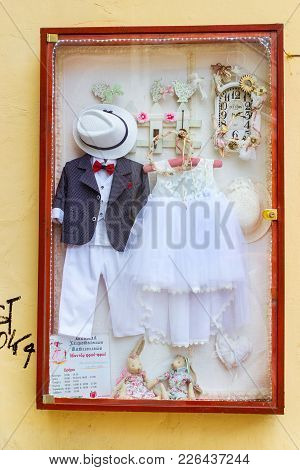 Rethymno, Greece - May 3, 2016: Miniature Wedding Suit And Bridesmaid Dress On Signboard Of Bridal S